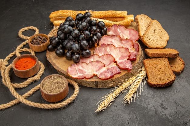 Fette di prosciutto vista frontale con condimenti all'uva e fette di pane su spuntino scuro foto a colori pasto alimentare a base di carne