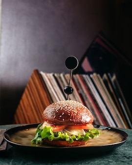 A front view hamburger inside round plate on the dark floor