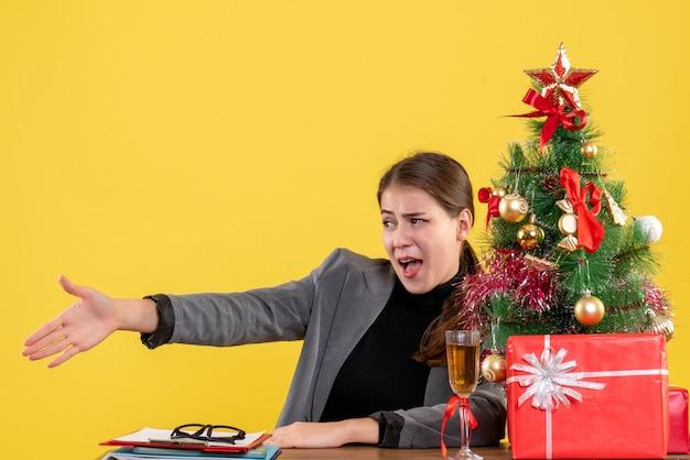 책상 크리스마스 트리와 선물 칵테일에 앉아 사려 깊은 소녀를주는 전면보기 손