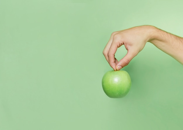 Front view of hand holding apple