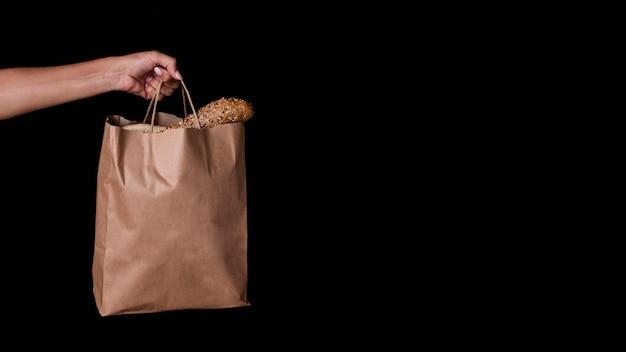 Вид спереди рука держит сумку с хлебом и копией пространства