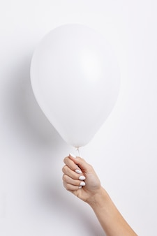 Front view of hand holding balloon