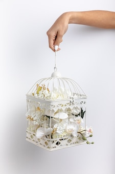 Front view of hand holding bird cage filled with flowers