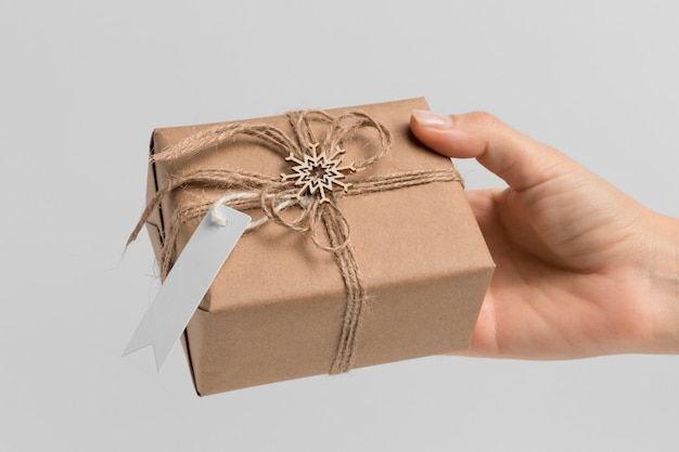 Front view of hand holding christmas gift
