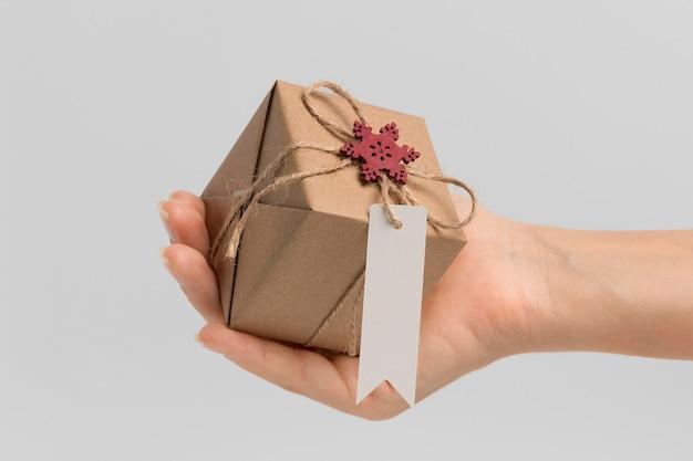 Vista frontale della mano che tiene il regalo di natale