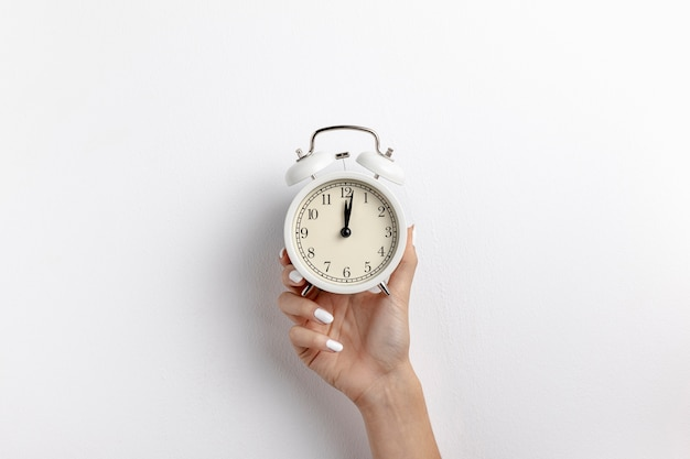 Front view of hand holding clock with copy space