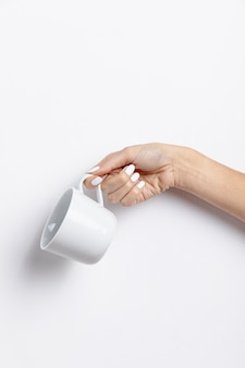 Front view of hand holding empty mug
