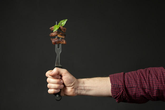 Front view of hand holding food on fork