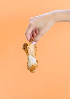Вид спереди рука, держащая остатки еды