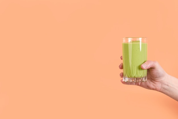 Front view hand holding green smoothie in glass with copy-space