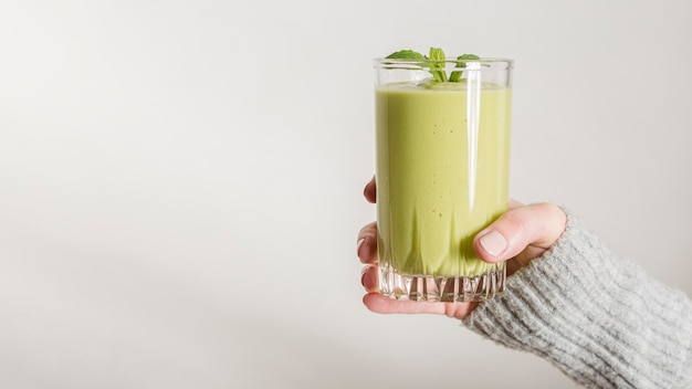 Front view hand holding green smoothie and mint in glass with copy-space
