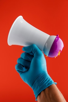 Front view of hand holding megaphone while wearing glove