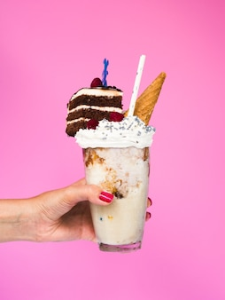 Front view of a hand holding a milkshake with pink background