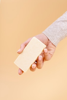Front view of hand holding one piece of wafer with copy space