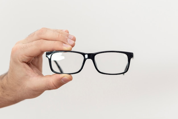 Front view of hand holding pair of glasses