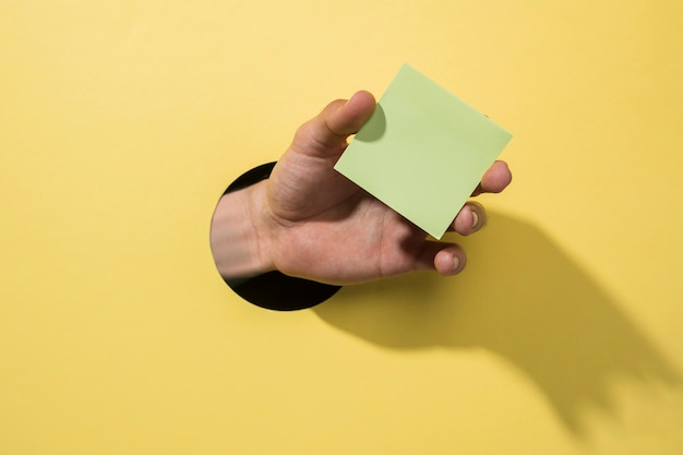 Front view hand holding a post-it