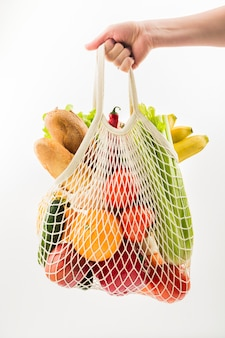 Front view of hand holding reusable bag with vegetables and fruit