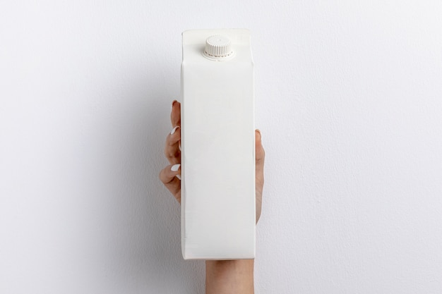 Front view of hand holding simple milk carton