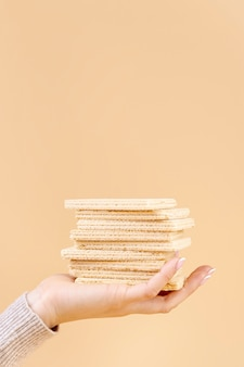 Front view of hand holding stack of wafers with copy space