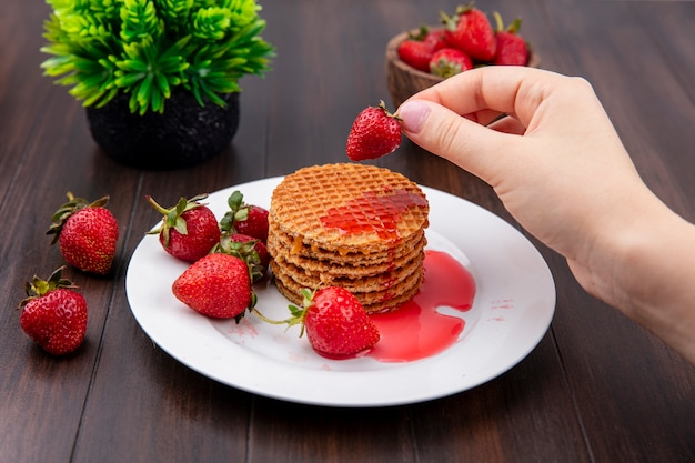 Front view of hand holding strawberry with waffle biscuits in plate and bowl of strawberry and flower on wooden surface