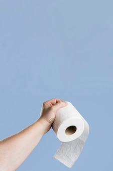 Front view of hand holding toilet paper with copy space