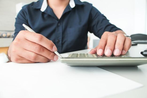 전면보기 손 남자 종이와 손가락 터치 계산기에 펜으로 쓰기. 작업 사무실 개념입니다. 작업 개념. 지불 개념. 계정 또는 재정. 구매 또는 구매자 개념.