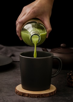 Front view of hand pouring matcha tea in cup