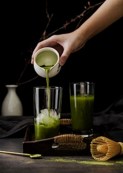 Front view of hand pouring matcha tea in glass on tray