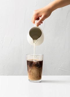 Front view of hand pouring milk in coffee glass