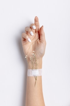 Front view of hand with adhesive bandage and flowers