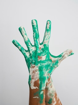 Front view of hands colored with paint
