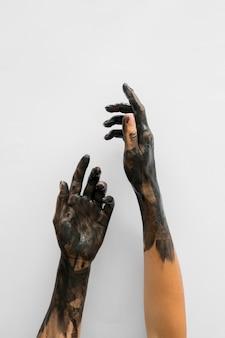 Vista frontale delle mani coperte di vernice nera con spazio di copia