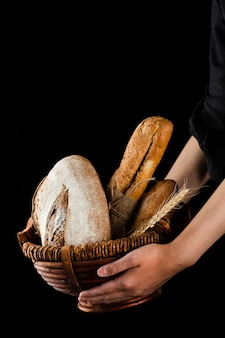 Front view of hands holding a basket with bread