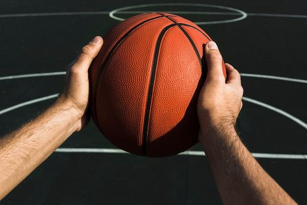 Вид спереди руки держат баскетбол
