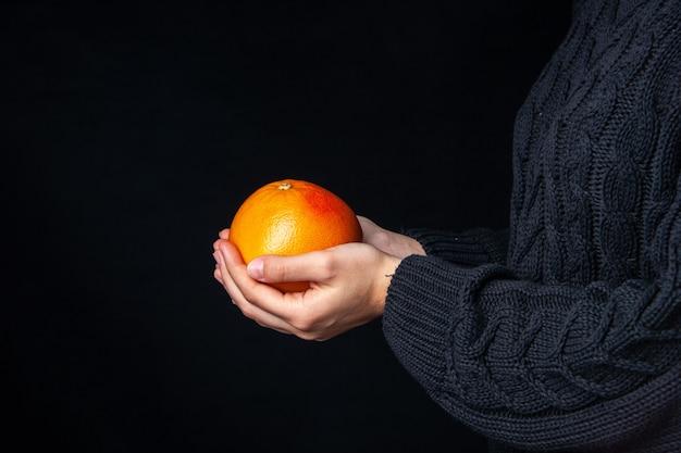 暗い表面に新鮮なオレンジを保持している正面図の手