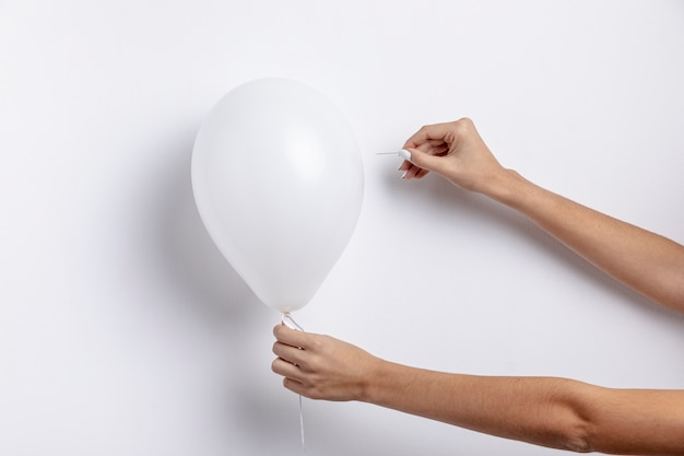 Front view of hands holding needle trying to pop balloon