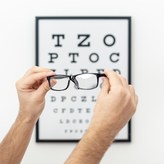 Front view of hands holding pair of glasses with defocused eye test in the background