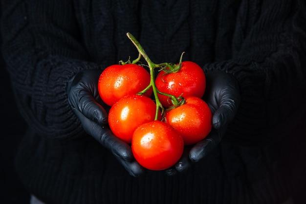 トマトの枝を保持している黒い手袋と正面図の手