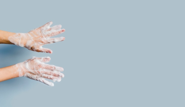 Front view of hands with foam from soap and copy space