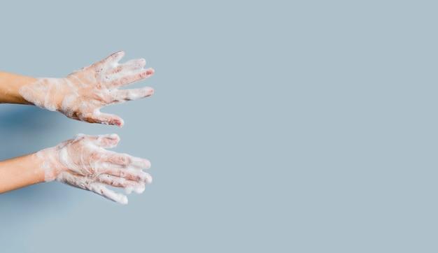 Vista frontale delle mani con schiuma dallo spazio di copia e sapone