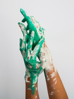 Front view of hands with paint over them