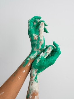 Vista frontale delle mani con vernice