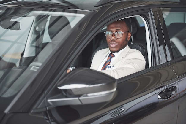 Front view of handsome african elegant serious business man drives a car.