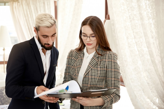 Front view of a handsome businessman and attractive businesswoman who are looking at the file with documents
