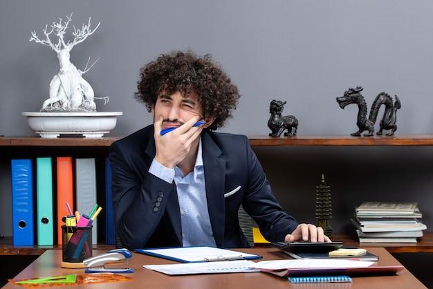 Vista frontale bell'uomo d'affari seduto alla scrivania pensando a qualcosa stock photo