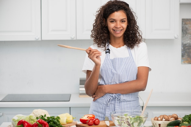 Front view handsome lady holding a wooden spoon