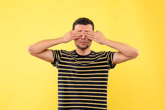 Front view handsome male in black and white striped t-shirt covering eyes with hands on yellow isolated background