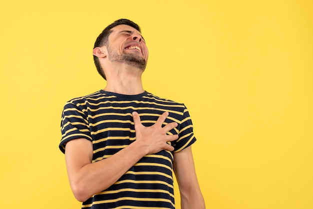 Front view handsome male in black and white striped t-shirt holding chest with pain on yellow isolated background