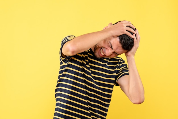 Front view handsome male in black and white striped t-shirt holding head with pain on yellow isolated background