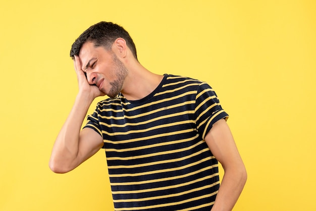 Vista frontale bel maschio in bianco e nero a strisce t-shirt tenendo la testa su sfondo giallo isolato
